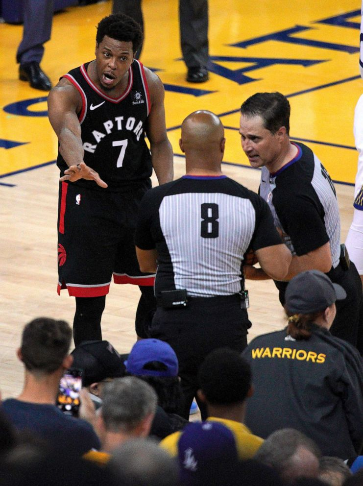 PHOTO: Toronto Raptors guard Kyle Lowry (7) gestures next to referees Marc Davis and Kane Fitzgerald near the front row of fans during the NBA Finals between the Golden State Warriors and the Raptors in Oakland, Calif., June 5, 2019.