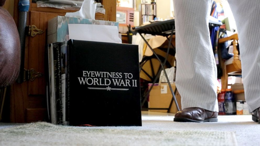"""Leatherman stands next to a book on the ground of his apartment that is entitled """"Witnesses of World War II"""". Leatherman was a mailman aboard the U.S.S. Oglethorpe in the Pacific Theater."""