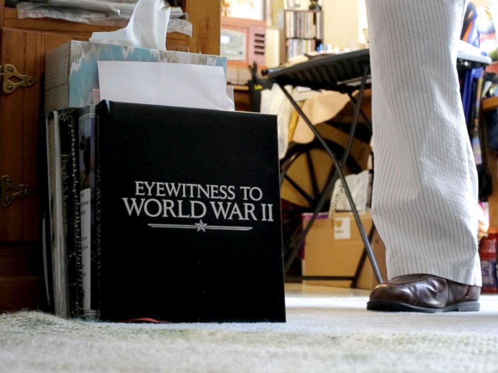 PHOTO: Leatherman stands next to a book on the ground of his apartment that is entitled Witnesses of World War II. Leatherman was a mailman aboard the U.S.S. Oglethorpe in the Pacific Theater.
