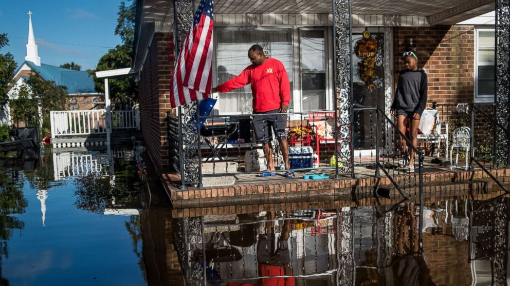 Robert Addison cooks breakfast on a charcoal grill with his son, Artis Addison, on Oct. 12, 2016 in a home surrounded by floodwater after Hurricane Matthew in Lumberton, N.C.