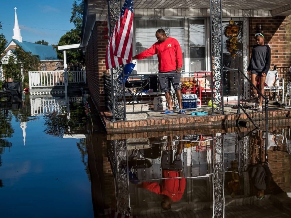 PHOTO: Robert Addison cooks breakfast on a charcoal grill with his son, Artis Addison, on Oct. 12, 2016 in a home surrounded by floodwater after Hurricane Matthew in Lumberton, N.C.