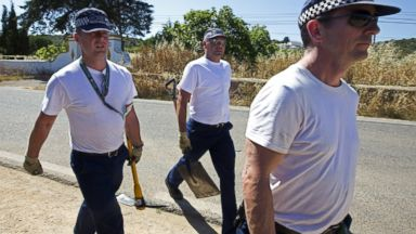 PHOTO: Scotland Yards officers carrying pickaxes and shovels leave after searching the area of scrubland near the holiday apartment where the British girl Madeleine McCann vanished seven years ago, in Praia da Luz in Portugal on June 11, 2014.