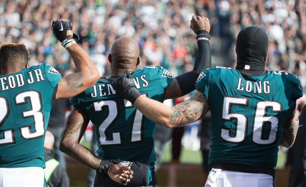 PHOTO: Rodney McLeod and Malcolm Jenkins of the Philadelphia Eagles raise their fists as teammate Chris Long #56 stands alongside them during the national anthem prior to the game against the Chicago Bears at Lincoln Financial Field on Nov. 26, 2017.