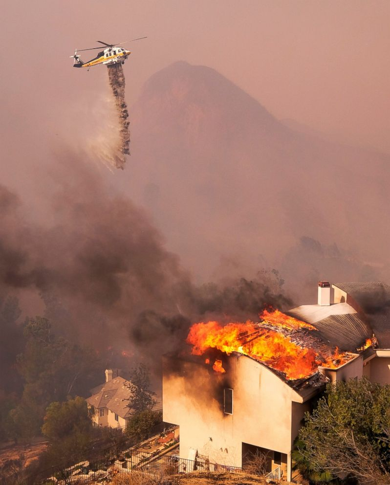 A helicopter drops water while a wildfire burns a home near Malibu Lake in Malibu, Calif., Friday, Nov. 9, 2018.