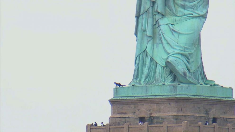 A woman appears to be climbing up the Statue of Liberty, July 4, 2018 in New York.