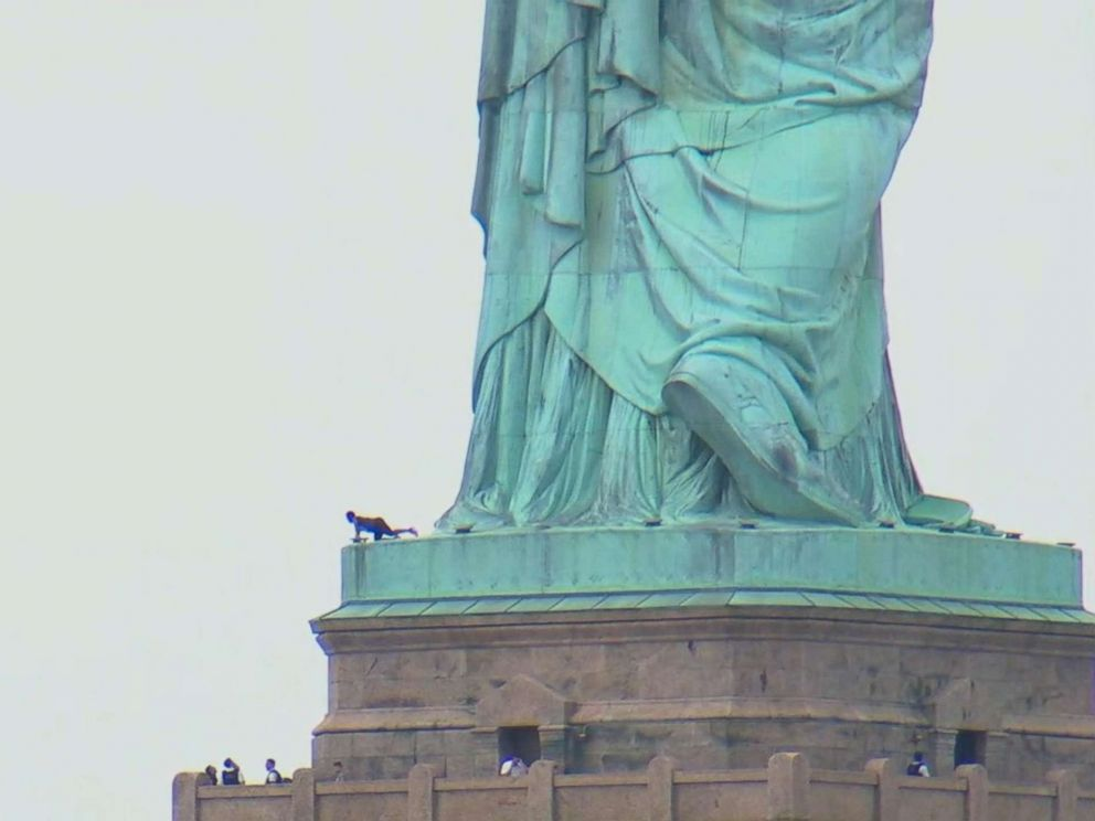 PHOTO: A woman appears to be climbing up the Statue of Liberty, July 4, 2018 in New York.