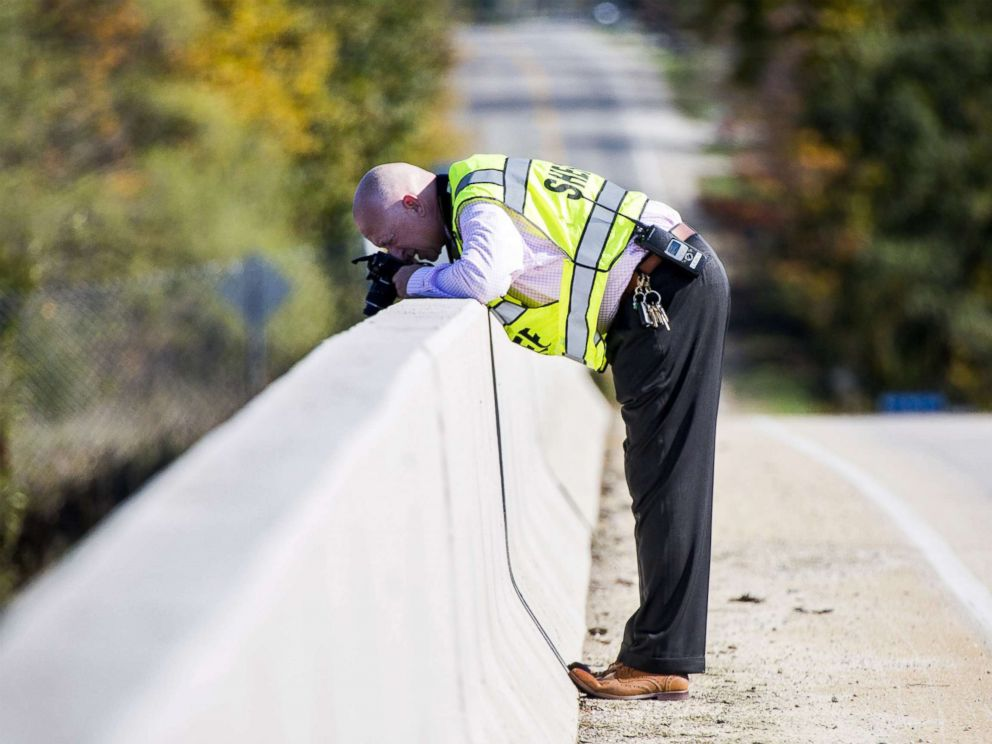 Genesee County Sheriffs Office investigator takes photos from an overpass on Oct. 20, 2017, in Vienna Township, Mich. where a rock was thrown from, smashing a car windshield and killing a 32-year-old man on Oct. 18.
