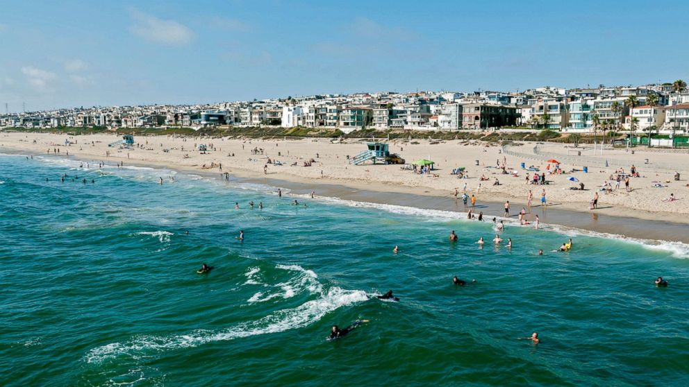 This stock photo depicts swimmers and surfers enjoying the water in Manhattan Beach, California.