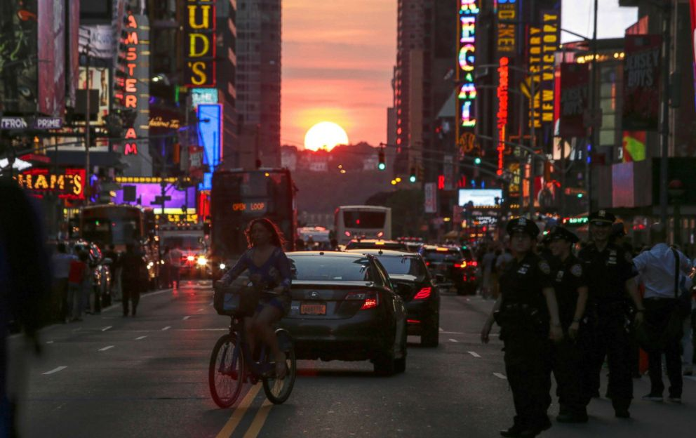 PHOTO: A woman rides a bike on 42nd Street in New York City during Manhattanhenge, July 12 2016.