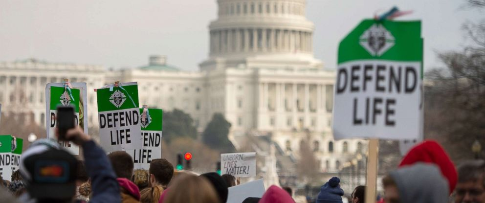 """PHOTO: Students and activists carry signs during the annual """"March for Life"""" in Washington, DC, Jan. 18, 2019."""