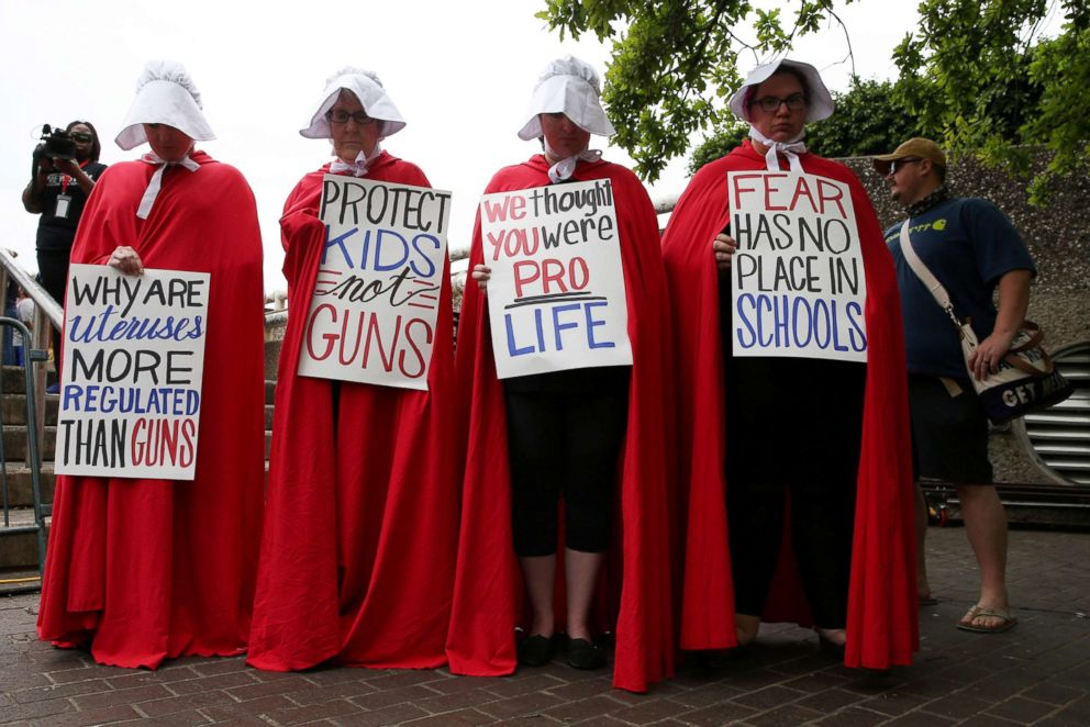 PHOTO: Activists wear red robes and white bonnets based on The Handmaids Tale before the March for Our Lives in downtown Houston, March 24, 2018.