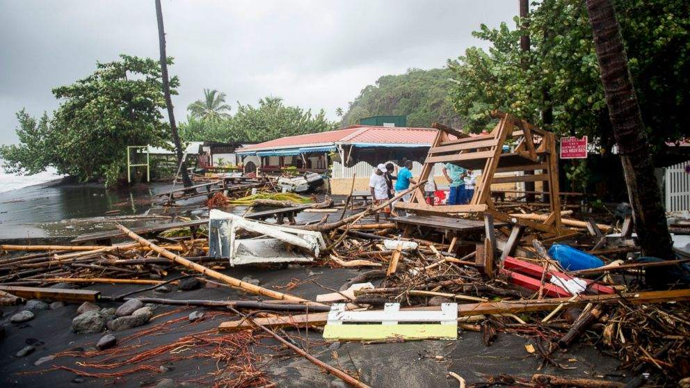 People stand among the debris at a restaurant in Le Carbet, on the French Caribbean island of Martinique, after it was hit by Hurricane Maria, on September 19, 2017.