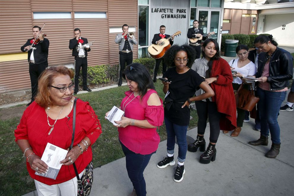 PHOTO: Latino voters Griselda Sanchez, left and Evelyn Franco, second from left, wait in line while being serenaded by mariachis at the Lafayette Park Gymnasium polling station in Los Angeles, Calif., Nov. 6, 2018.