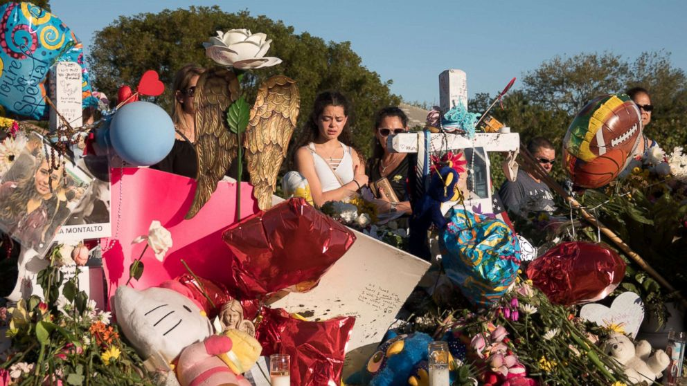 People are pictured at a memorial the day students and parents arrive for voluntary campus orientation at the Marjory Stoneman Douglas High School following last week's mass shooting in Parkland, Fla., Feb. 25, 2018.