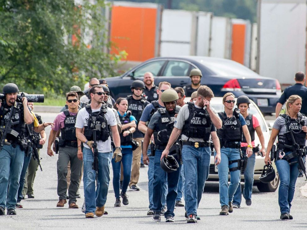 PHOTO: Agents on patrol after clearing an area near a warehouse as police search for a gunman who fled the scene of a shooting at a Rite Aid Distribution Center in Aberdeen, Maryland,Sept. 20, 2018.