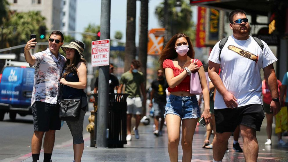 PHOTO: People walk and take photos on Hollywood Boulevard, June 15, 2021, in Los Angeles.