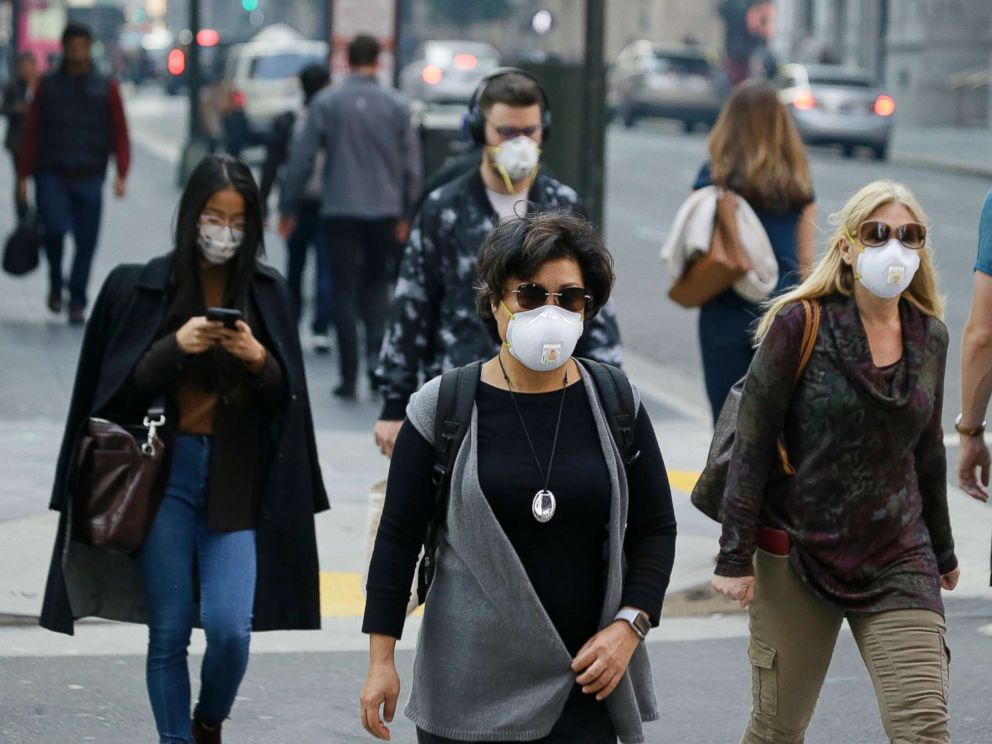 PHOTO: People wear masks while walking through the Financial District in the smoke-filled air, Nov. 9, 2018, in San Francisco. Authorities have issued an unhealthy air quality alert for parts of the San Francisco Bay Area due to the wildfires.
