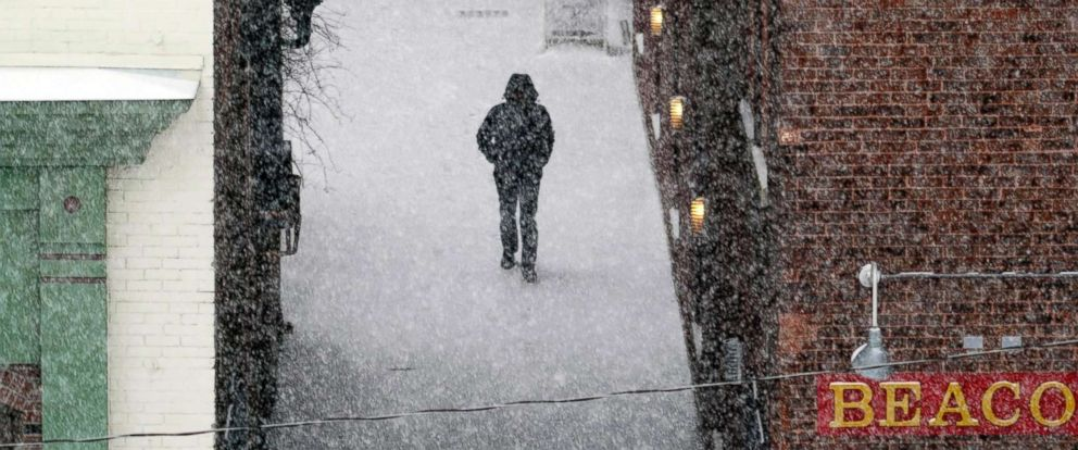 PHOTO: A man walks down an alley to McKay Street as snow falls in Pittsfield, Mass., Feb, 12, 2019.