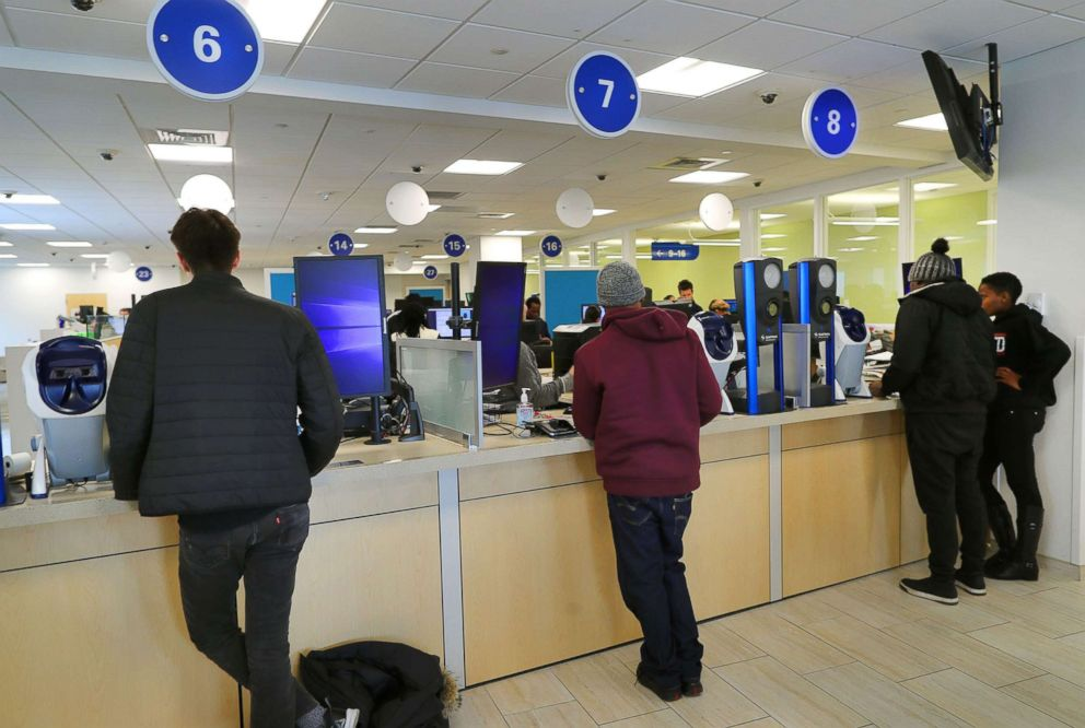 PHOTO: Customers wait to get their drivers licenses at a counter in the Haymarket Registry of Motor Vehicles office in Boston on March 21, 2018.