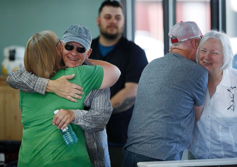 Supporters of baker Jack Phillips, owner of Masterpiece Cakeshop, hug inside Phillips' shop, June 4, 2018, in Lakewood, Colo.