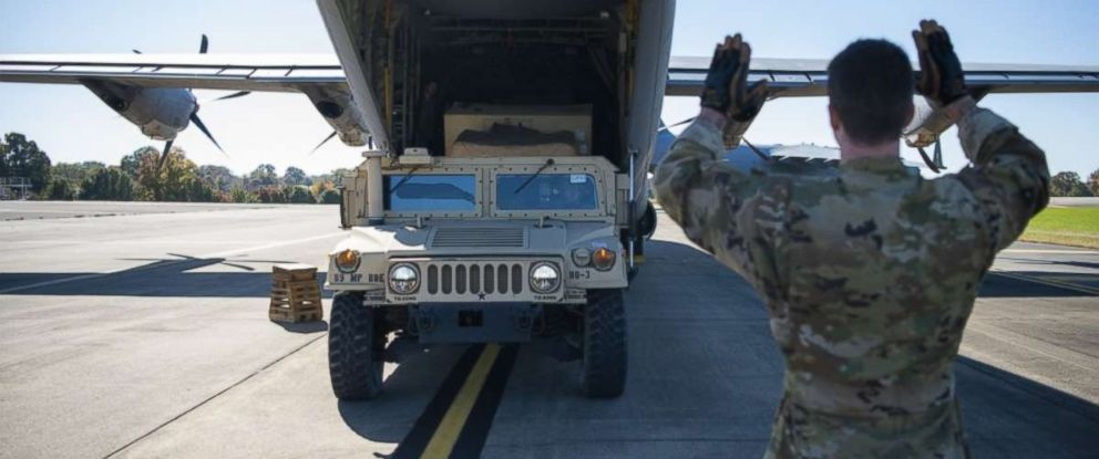 PHOTO: Airman 1st Class Nicholas Mariner, loadmaster with the 61st Airlift Squadron, Little Rock, AR, directs a HMMWV into a C-130J Super Hercules at Fort Knox, KT, in support of Operation Faithful Patriot on October 29, 2018.