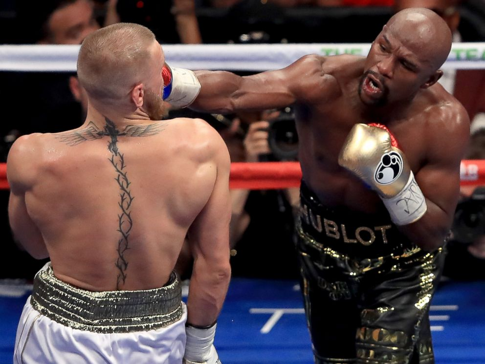 PHOTO: Floyd Mayweather Jr. throws a punch at Conor McGregor during their super welterweight boxing match on August 26, 2017 at T-Mobile Arena in Las Vegas, Nevada.