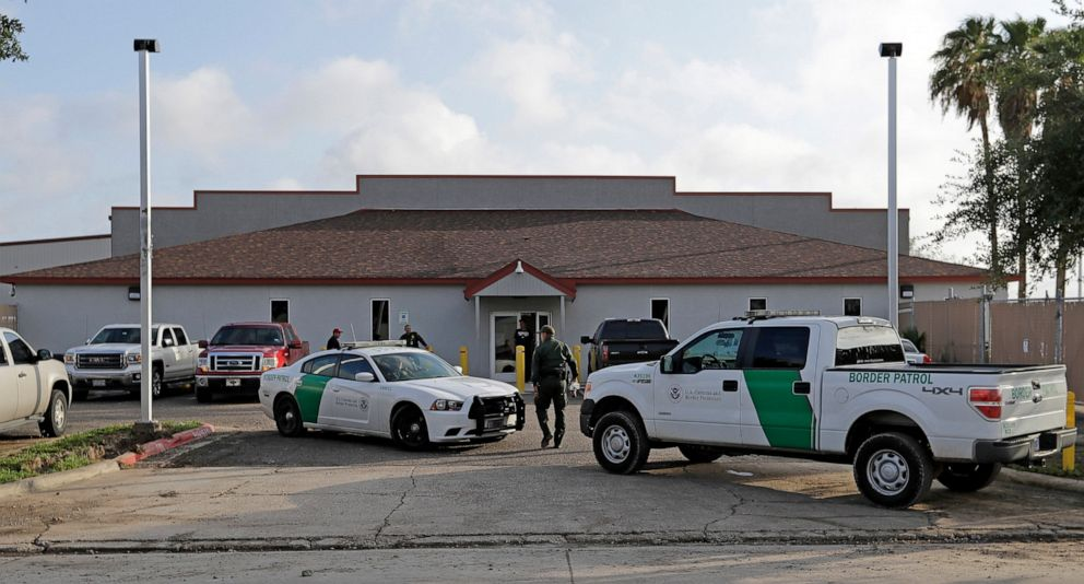PHOTO: A U.S. Border Patrol Agent walks between vehicles outside the Central Processing Center in McAllen, Texas.