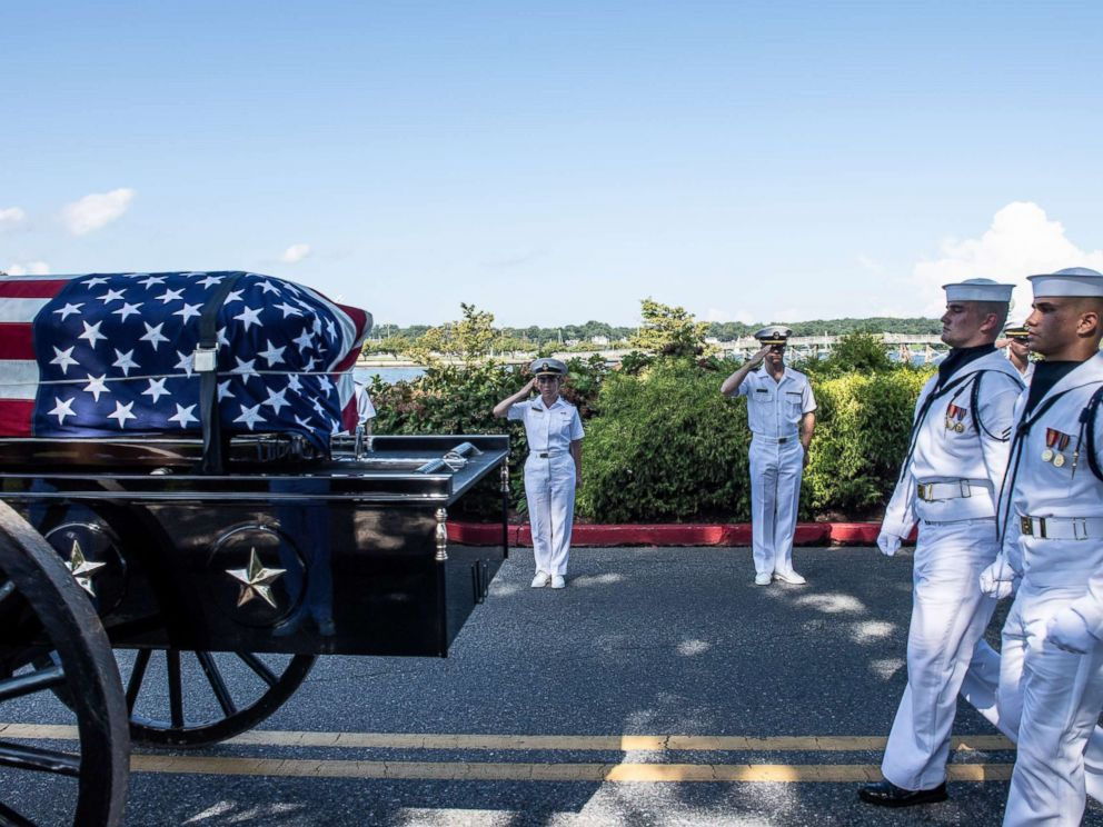 Midshipmen salute the late Sen. John McCain as a horse-drawn caisson transports his flag-draped casket to the United States Naval Academy Cemetery for his burial service, Sept. 2, 2018.