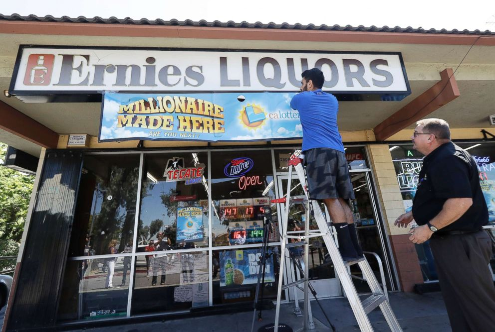 PHOTO: California Lottery official Mike Neis, right, watches as Amol Sachdev hangs a sign over his familys store Ernies Liquors in San Jose, Calif., July 25, 2018.