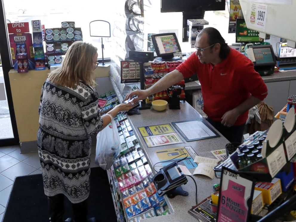 PHOTO: A cashier checks out a customer at a Lukoil service station where the winning ticket for the Mega Millions lottery drawing was sold, March 31, 2018, in Riverdale, N.J.