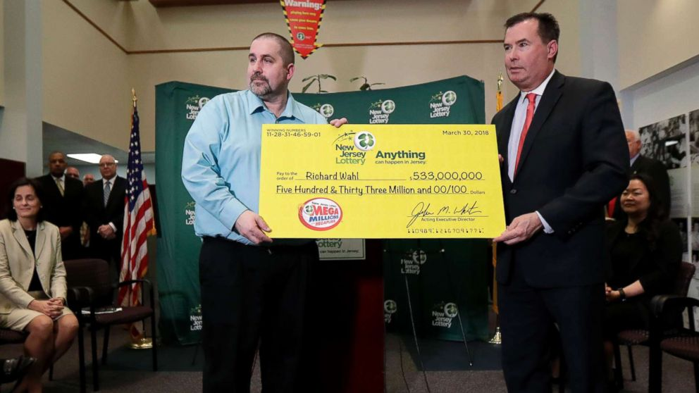 Richard Wahl poses for photos with the New Jersey Lottery Acting Executive Director during a news conference introducing Wahl as the $533 million Mega Millions jackpot winner at the New Jersey Lottery headquarters, April 13, 2018, in Trenton, N.J.