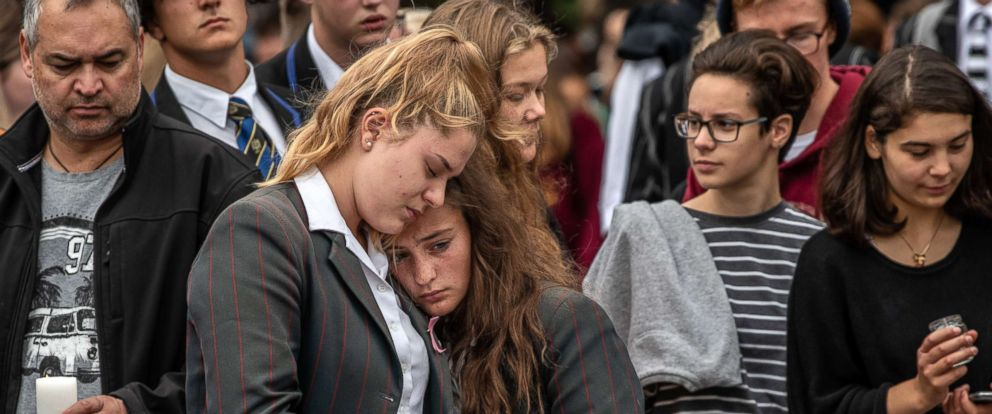 PHOTO: Schoolgirls comfort each other as they view flowers and tributes near Al Noor mosque, March 18, 2019, in Christchurch, New Zealand.