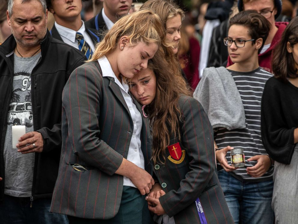 PHOTO: Schoolgirls comfort each other as they view flowers and tributes near Al Noor mosque, March 18, 2019 in Christchurch, New Zealand.