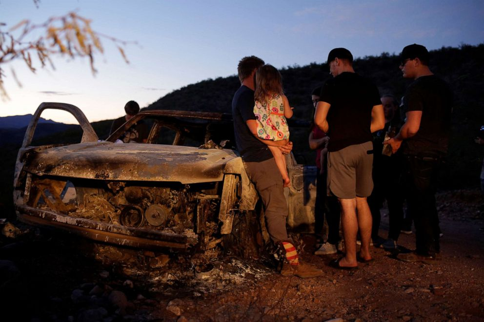 PHOTO: Relatives of slain members of Mexican-American families belonging to Mormon communities observe the burnt wreckage of a vehicle where some of their relatives died, in Bavispe, Sonora state, Mexico Nov. 5, 2019.