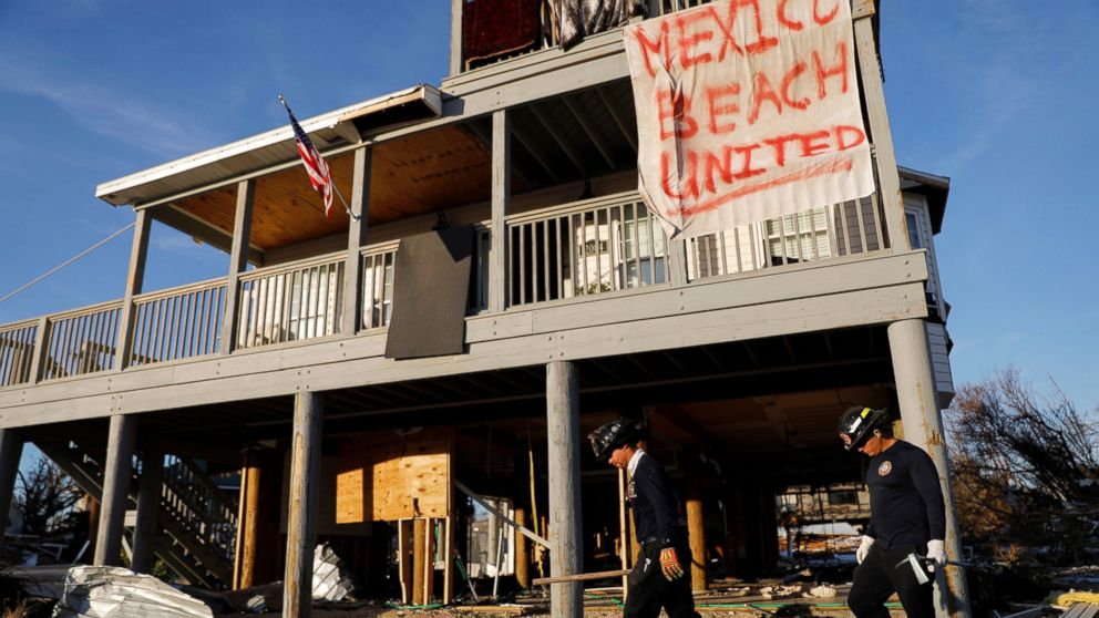 A banner hangs from a damaged home as a South Florida urban search and rescue team checks for survivors of hurricane Michael in Mexico Beach, Fla., Friday, Oct. 12, 2018.