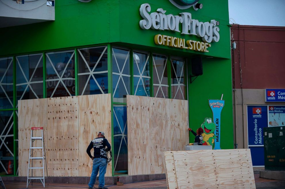 PHOTO: Workers protect a storefront with wood panels at the Mazatlan port in Sinaloa, Mexico, on Oct. 22, 2018, before the arrival of Hurricane Willa.