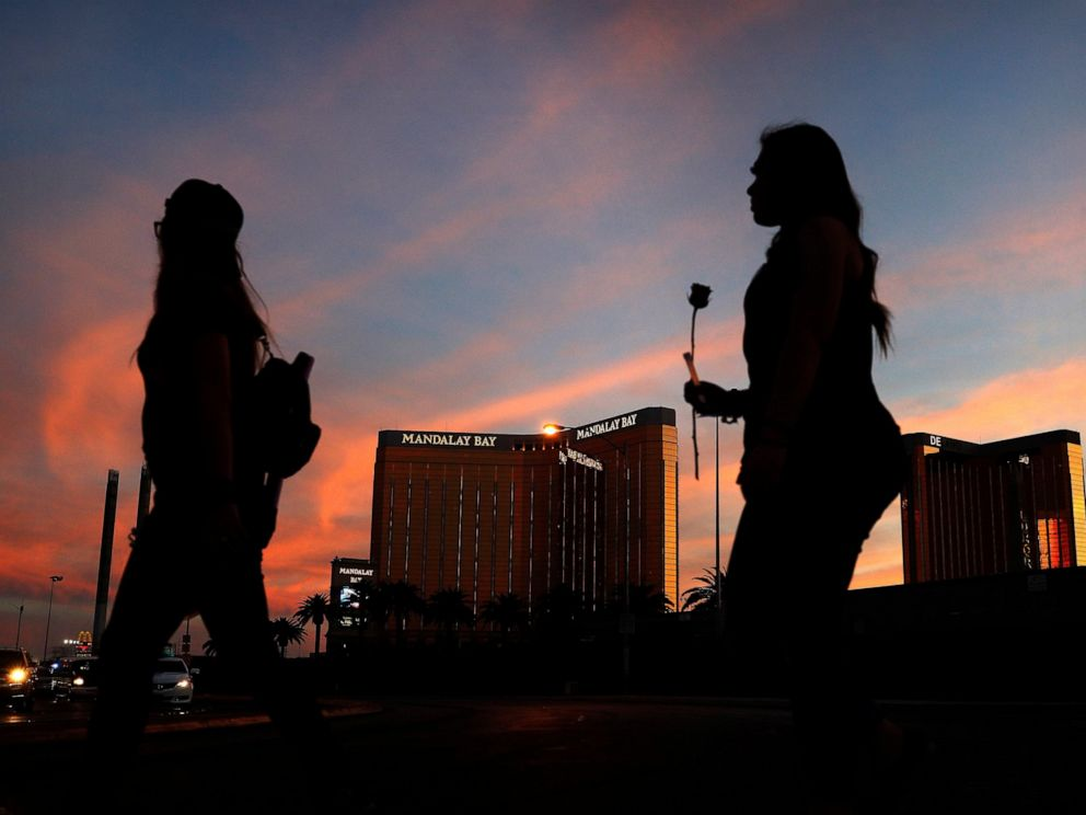 PHOTO: In this April 1, 2018, file photo, people carry flowers as they walk near the Mandalay Bay hotel and casino during a vigil for victims and survivors of a mass shooting in Las Vegas.