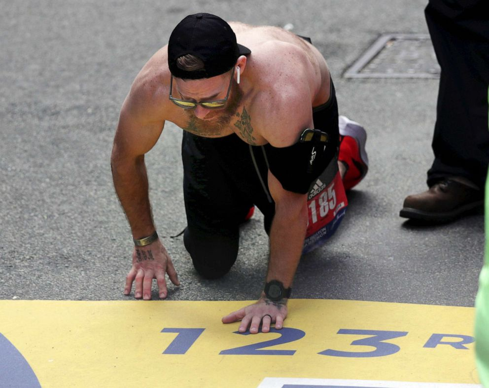 PHOTO: Micah Herndon, of Tallmadge, Ohio, crawls to the finish line in the 123rd Boston Marathon on April 15, 2019, in Boston.