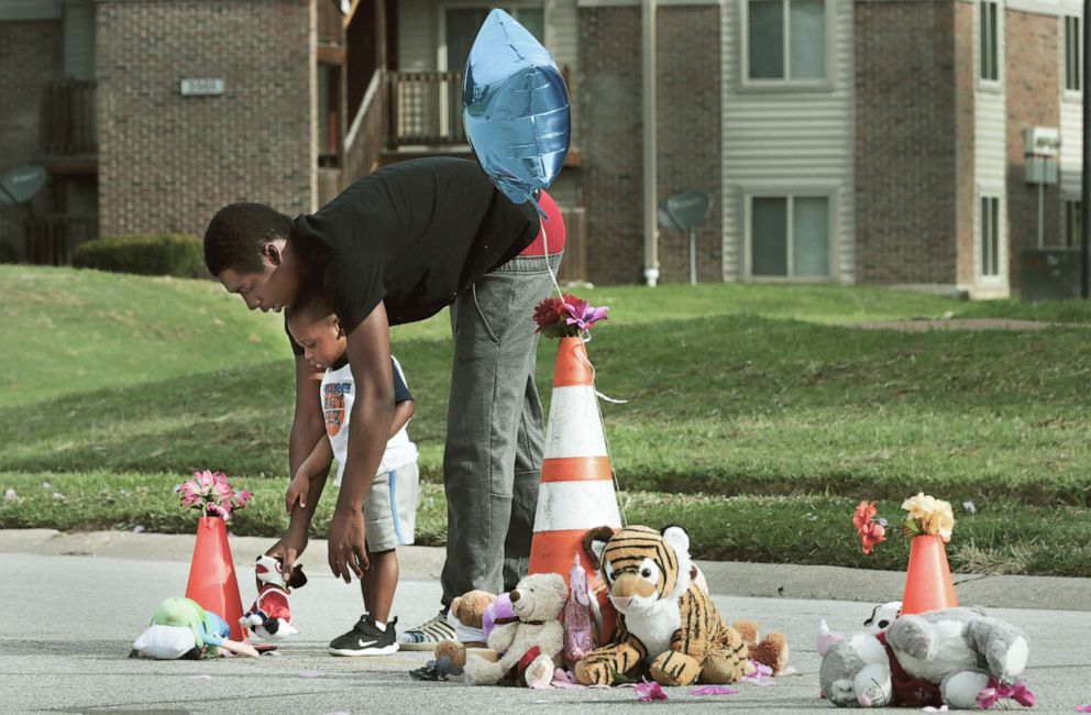 PHOTO: Canfield Green Apartments resident Marcus Hill helps his son Messiah Hill, 2, place a stuffed animal at a newly rebuilt memorial to Michael Brown, Jr. on Thursday, Aug. 8, 2019, in Ferguson, Mo.