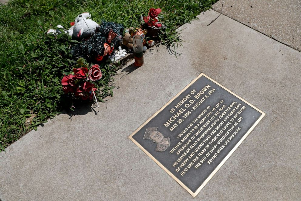 PHOTO: In this July 25, 2019, photo, flowers and other items lay near a memorial plaque in the sidewalk near the spot where Michael Brown was shot and killed by a police officer five years ago in Ferguson, Mo.