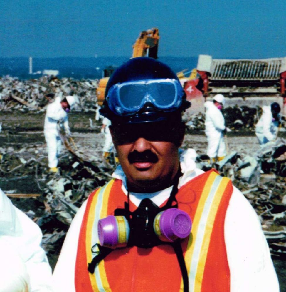 PHOTO: NYPD Sergeant Michael Guedes is pictured at the Fresh Kills landfill in Staten Island, New York, while workers sort through debris from the 9/11 attack in the background.