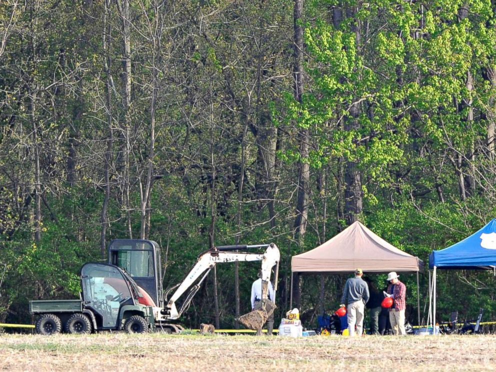 PHOTO: Investigators set up their equipment under tents before beginning their work at a dig site along a rural wooded area in Macomb Township, Mich., May 9, 2018.
