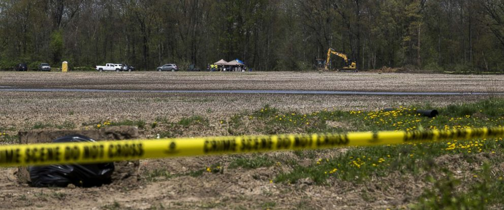 PHOTO: Crew members dig for human remains in a field and tree-line behind a subdivision on May 9, 2018 in Macomb, Mich.