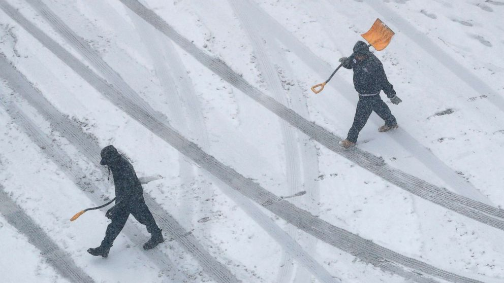 Workers carry snow shovels as snow falls, Nov. 25, 2018, in downtown Kansas City, Mo.