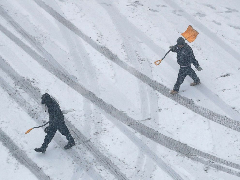 PHOTO: Workers carry snow shovels as snow falls, Nov. 25, 2018, in downtown Kansas City, Mo.