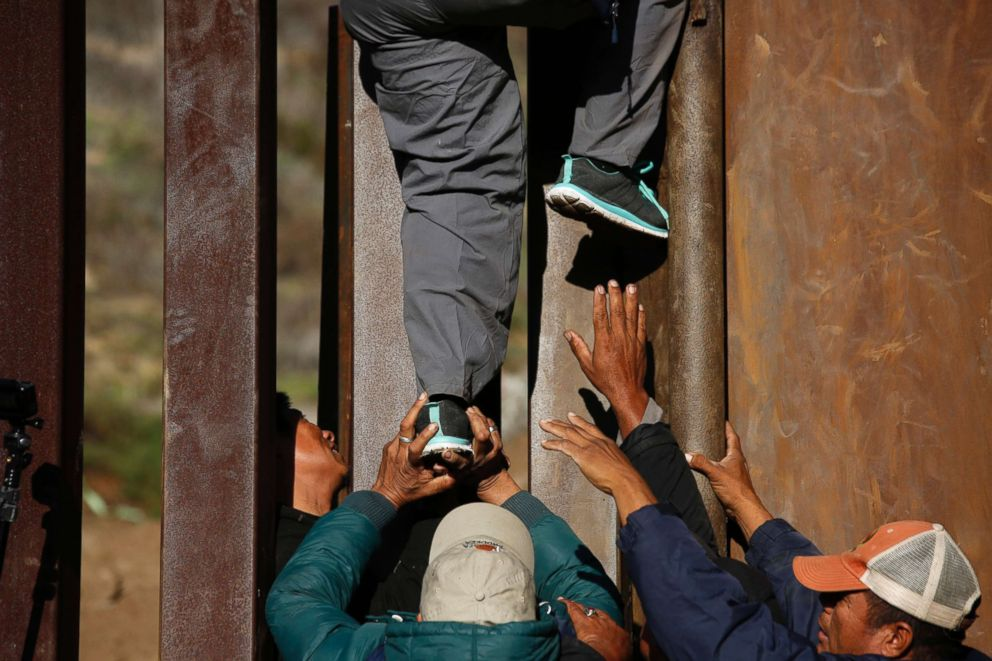 PHOTO: Honduran migrants help each other cross over the U.S. border wall to San Diego, from Playas in Tijuana, Mexico, Dec. 12, 2018.