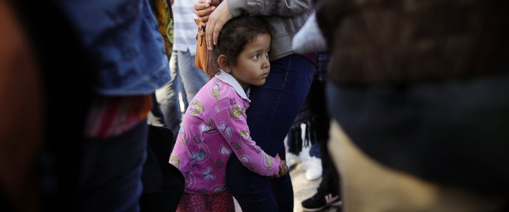 In this June 13, 2018 file photo, Nicole Hernandez, of the Mexican state of Guerrero, holds on to her mother as they wait with other families to request political asylum in the United States, across the border in Tijuana, Mexico.