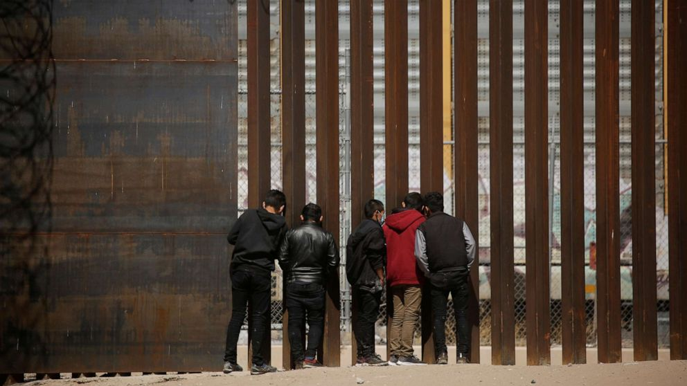 PHOTO: Migrants look through the border wall after crossing the Rio Bravo river to turn themselves in to U.S. Border Patrol agents and request asylum in El Paso, Texas, U.S., as seen from Ciudad Juarez, Mexico March 14, 2021.
