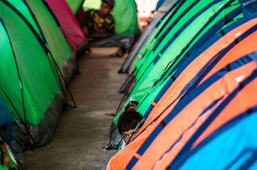 A Mexican migrant boy emerges next to tents at a shelter in Tijuana, Baja California state, Mexico, in the border with the U.S., Oct. 22, 2018.