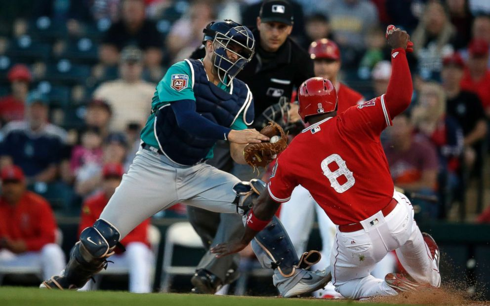 PHOTO: Seattle Mariners catcher Mike Marjama, left, tags out Los Angeles Angels left fielder Justin Upton trying to score in the first inning at Tempe Diablo Stadium.